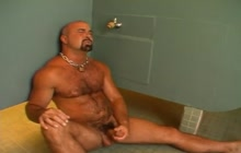 Pissing on horny bear while her is jerking off