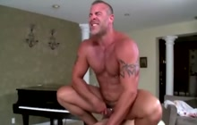 Muscled guy rides cock on massage table